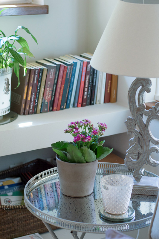 A little vignette with a vintage mirror top side table, a table lamp and a bookcase by a bay window in a home.