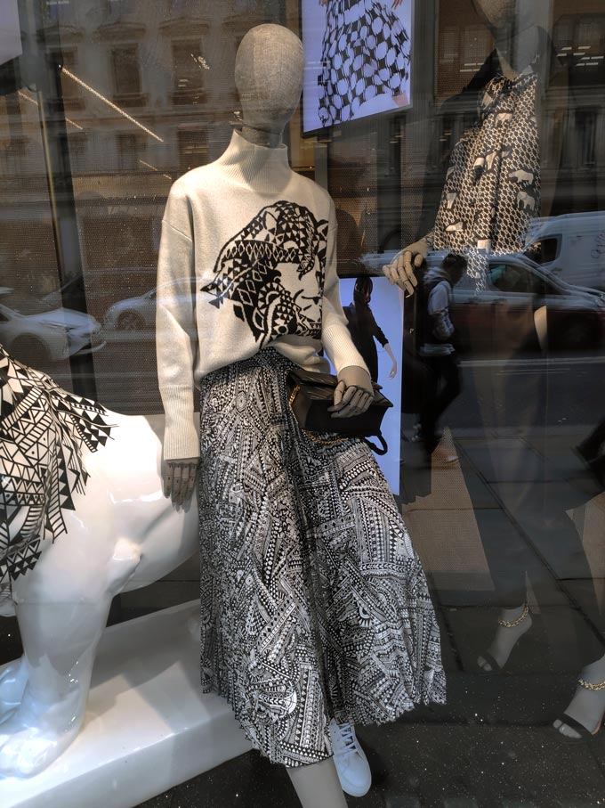 Two mannequins dressed in stylish black and white outfits part of a Hugo Boss shop window.