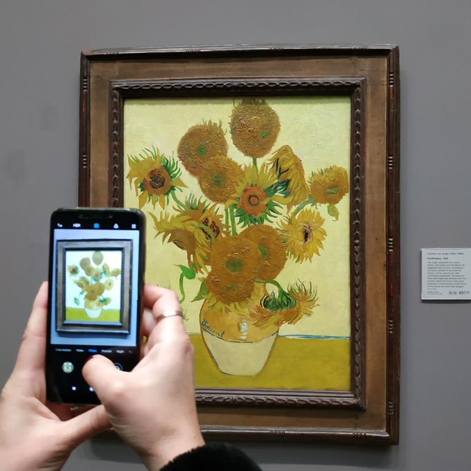 While snapping a shot with a smartphone of Van Gogh's Sunflowers.