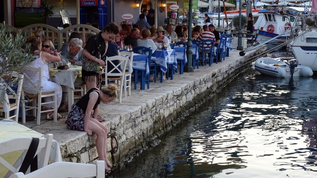 People eating by a seaside taverna by the marina of Fiscardo in Kefalonia.