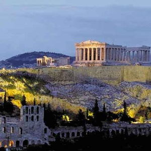 The Parthenon on the right and the Odeon on the left foot of the Acropolis in Athens lit at night.