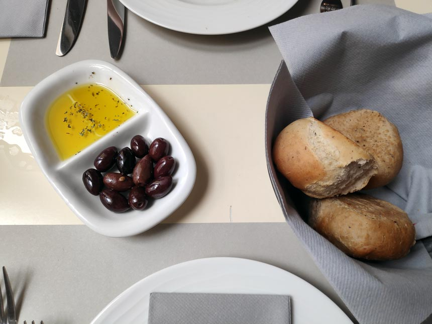 Olives and olive oil along with bread buns as an horderve.