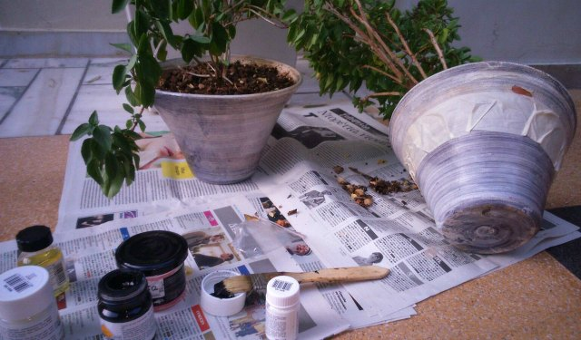 Two old gray planters being prepared with masking tape, paint and brushes for a makeover.