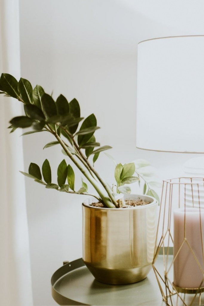 A gold planter next to a table lamp and decor on a side table.