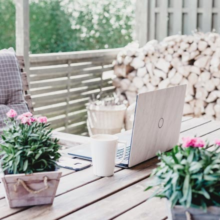 A white laptop on a table outdoors with two planters next to it.