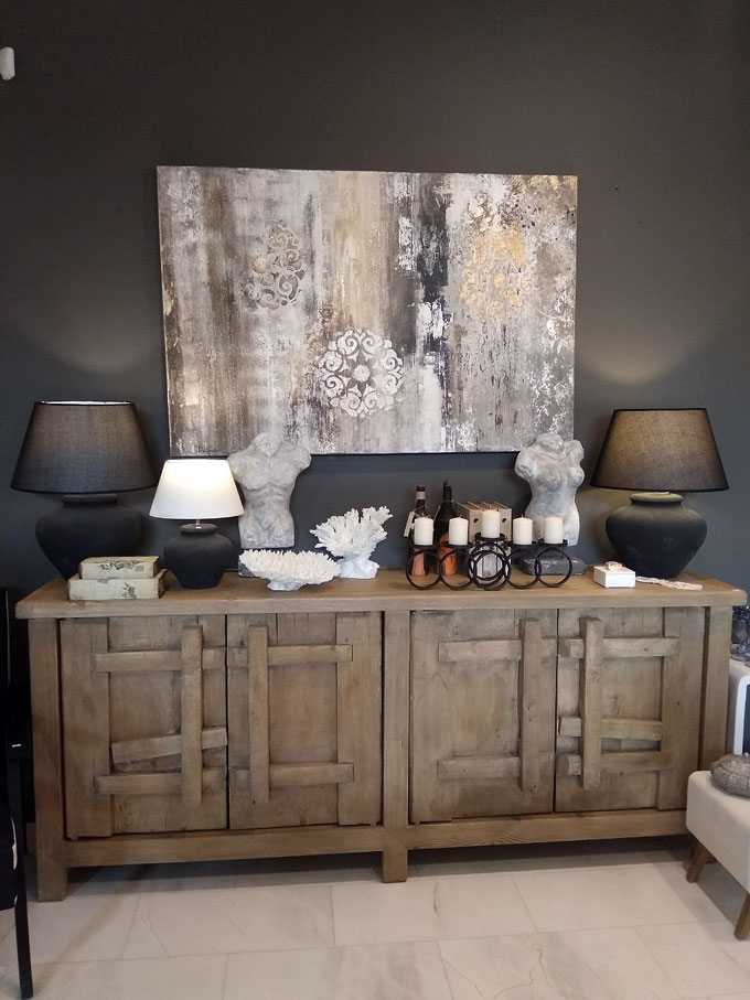 A large sideboard with an artwork on top of it, against an almost black wall. Decor pieces and black table lamps complete the synthesis.