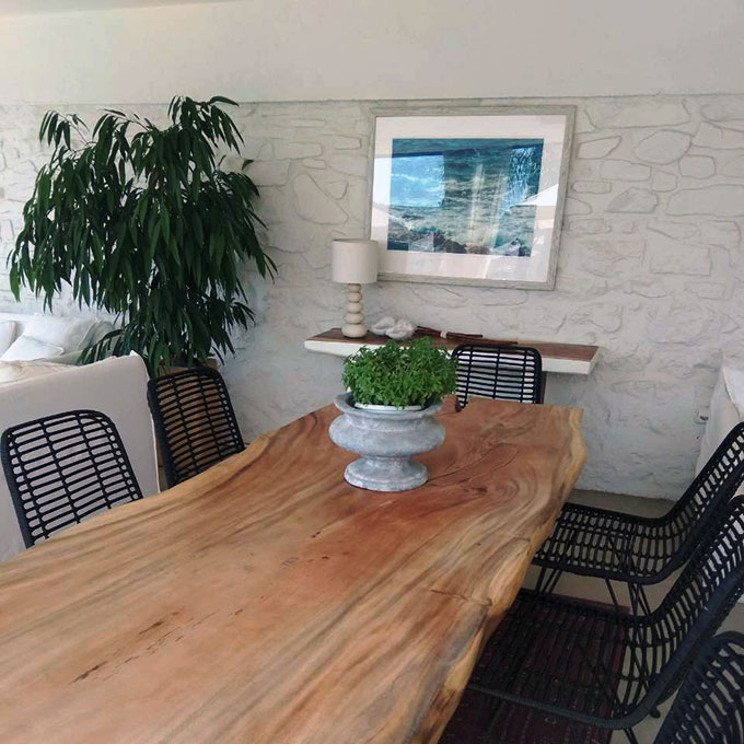 View of a dining space with a large rustic wooden table, black rattan dining chairs and a white stone wall in the background. Greenery as splashes liven it all up.
