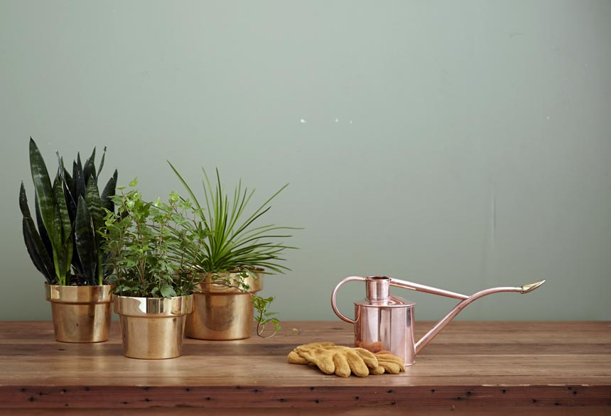 A cluster of three copper looking planters on a wooden surface.