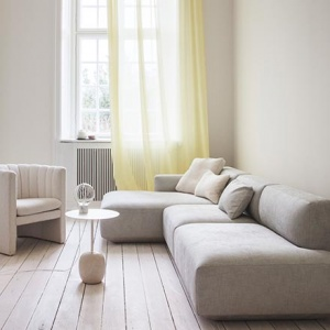 A soft minimal interior with an off white sectional sofa and armchair, the Lato side table with a table lamp atop and a large window casting lots of natural light. Image by Nest.