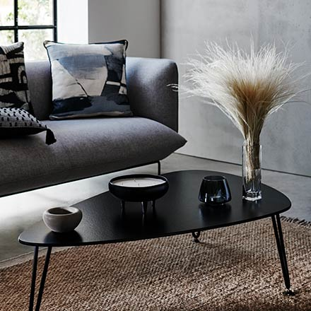 View of a vignette with a grey sofa, a black coffee table, and a large window in the background. Image via Sainsbury's Home.