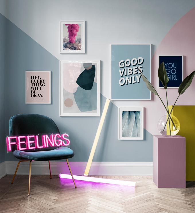 A vignette with a pop vibe to it, featuring a color blocked wall with an art gallery, a velvet upholstered armchair with a neon sign that reads feelings. Image by Desenio.