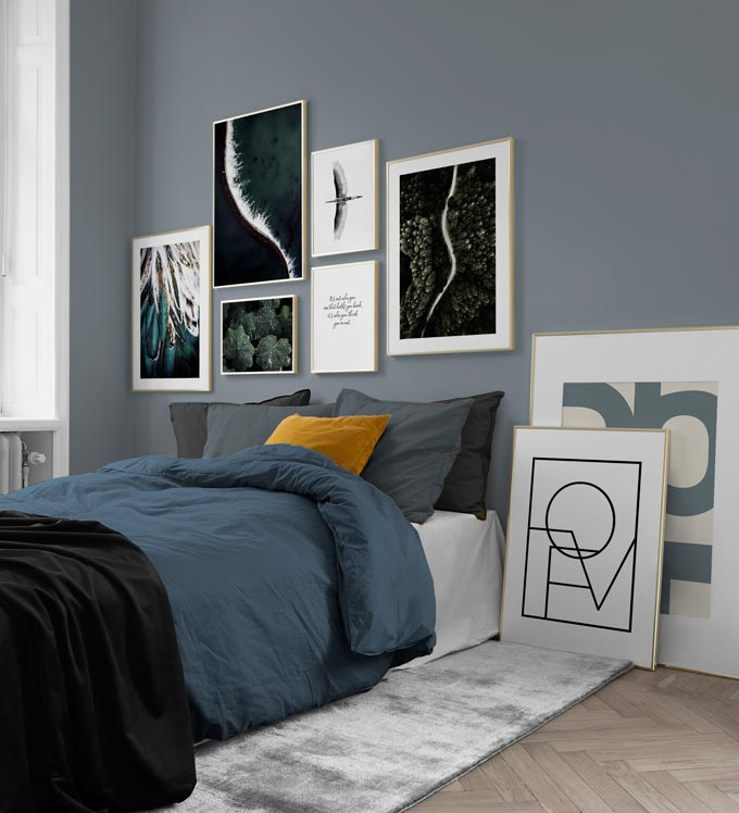 A contemporary bedroom in a grey blue color palette, featuring a gallery wall including some prints with typography.