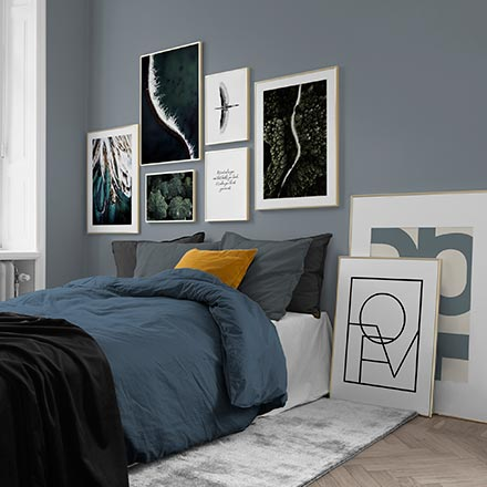 A contemporary bedroom in a blue color palette featuring a gallery wall that includes typography prints. Image by Desenio.