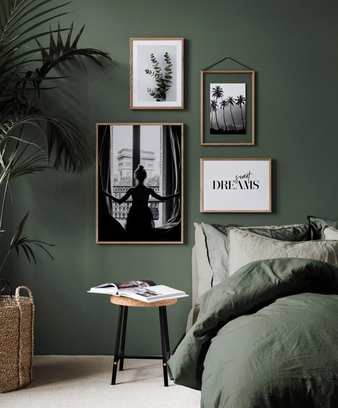 A contemporary green bedroom featuring a black and white gallery wall that includes some typography. Image by Desenio.