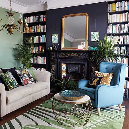 Loving the mix of green and mauve on the walls. A stylish living room with a purple accent wall and fireplace in mauve and bookcases on either side of it. Image by Dunelm.