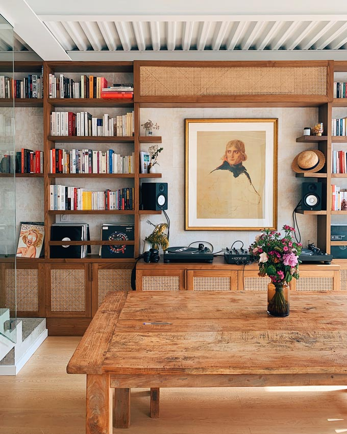 A room with a bookcase and a large wooden dining table.