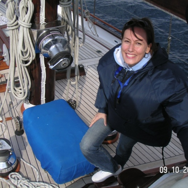 Velvet on a sailing boat's deck wearing a navy blue windproof jacket and a pair of jeans