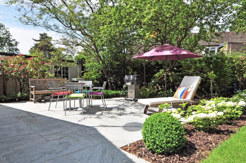 A beautiful backyard with a chaise longue, dining setup, sun umbrella during the daylight.