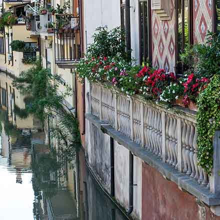 A closer view of a residential narrow balcony with planters that overlooks a canal in an Italian city