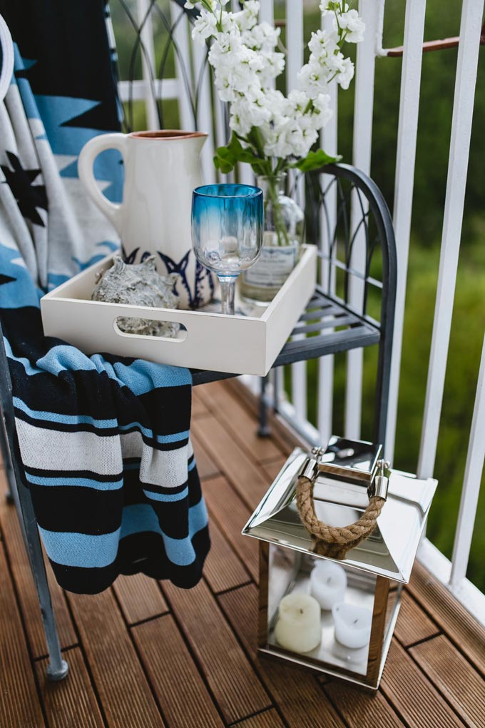 A narrow balcony with a chair and lots of nautical theme decor including a lantern.