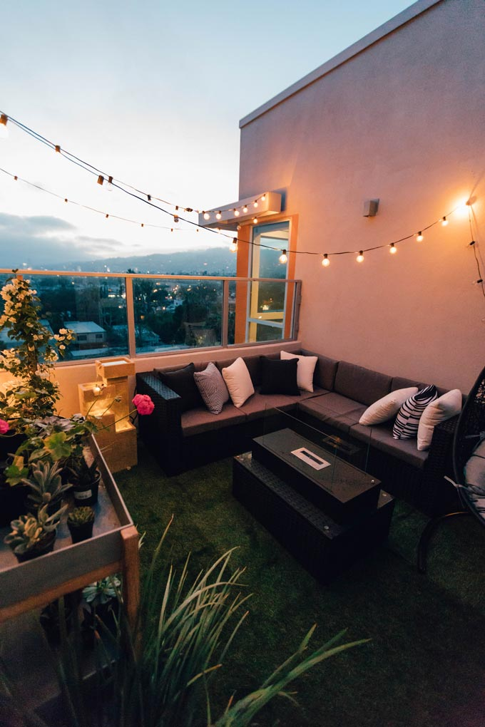 A private roof garden with a string of lights hanging over a sectional sofa.