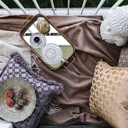 An exotic setup with throws, pillows at a balcony