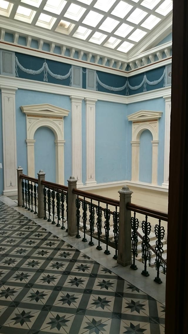 Partial view of a corridor and the main stairwell inside the town hall in Hermoupolis, Syros