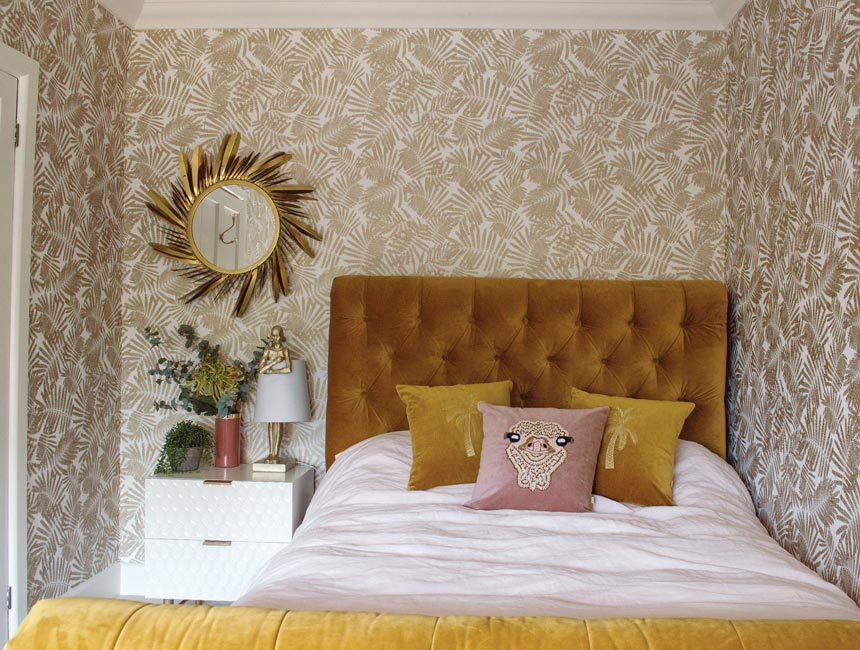 A bedroom with an gold leaf pattern wallpaper, a mustard hue bed and decorative pillows on top of the white bedding. Image via Audenza.