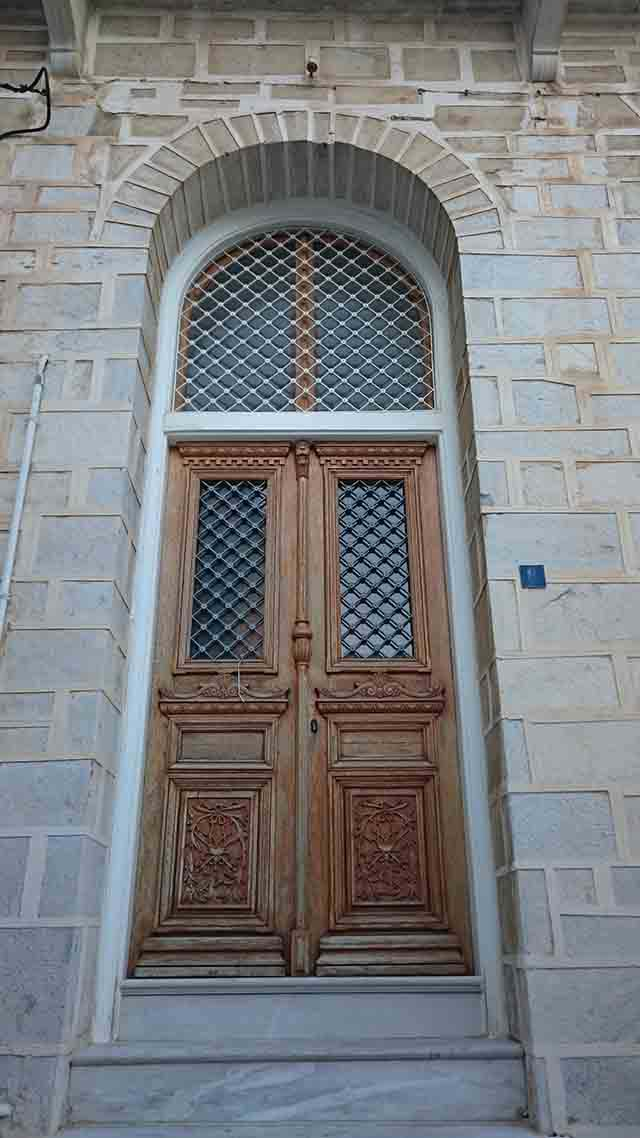 An old wooden entrance door to a stone building in Syros