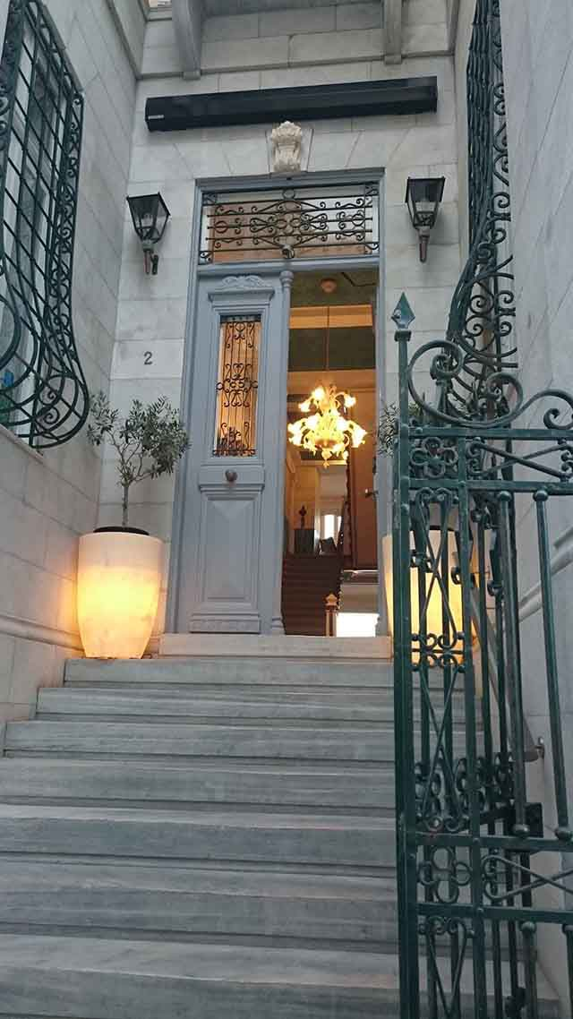 View of the grand entrance to a boutique hotel in Syros with typical architectural features found in the island