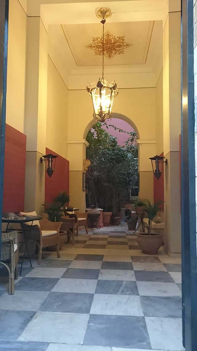 Image of an entrance way to a hotel with a very high ceiling painted with a mural and a marble chess floor with sitting arrangements like a narrow patio