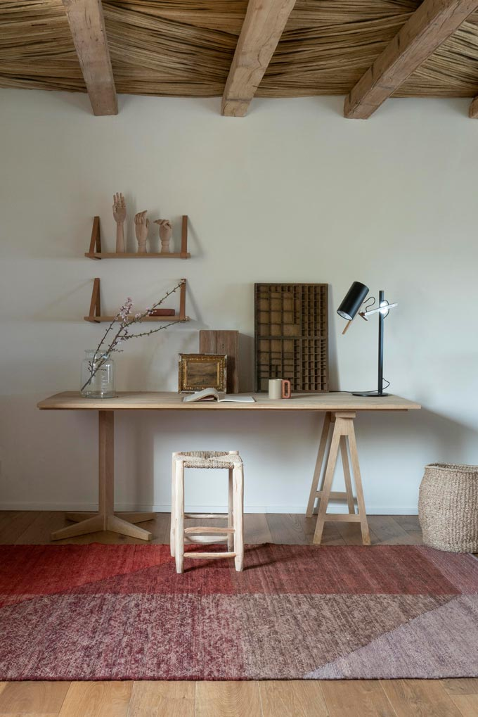 A red pattern area rug in front of a rustic home office. Image via Nest.co.uk.