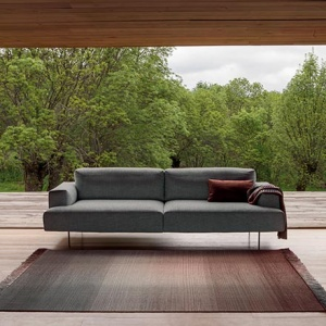 An ombre designer rug in front of a grey sofa. In the background a stunning garden view through an enormous window from floor to ceiling. Image via Nest.co.uk.