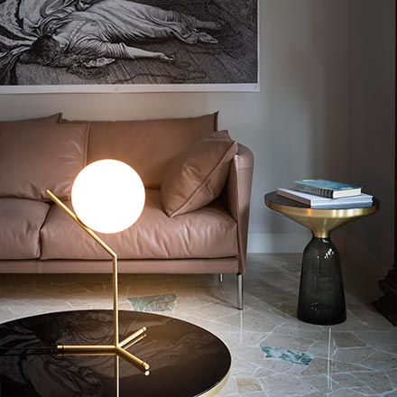 View of a vignette with a leather sofa, a glass side table and the IC T1 high table lamp designed by Michael Anastassiades on a glass coffee table. Image via Nest.co.uk.