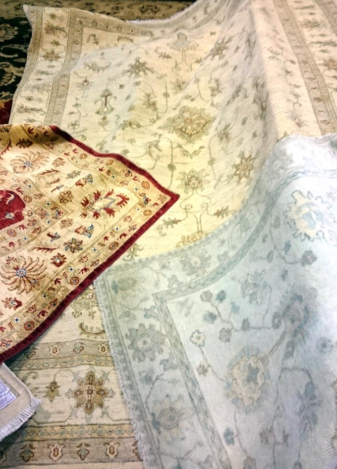 Partial view of three different Zieger rugs that showcase the differences in coloring over the years.