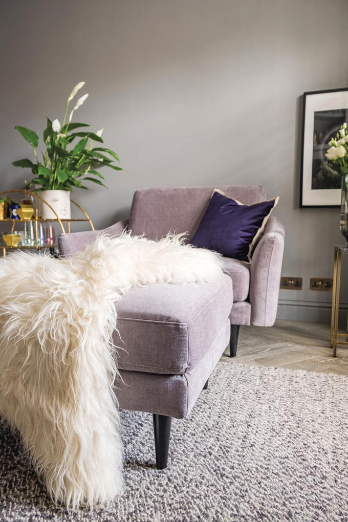 A vignette with a soft purple armchair and coordinating footstool that has a shuggy rug atop. Image via Snug Shack.