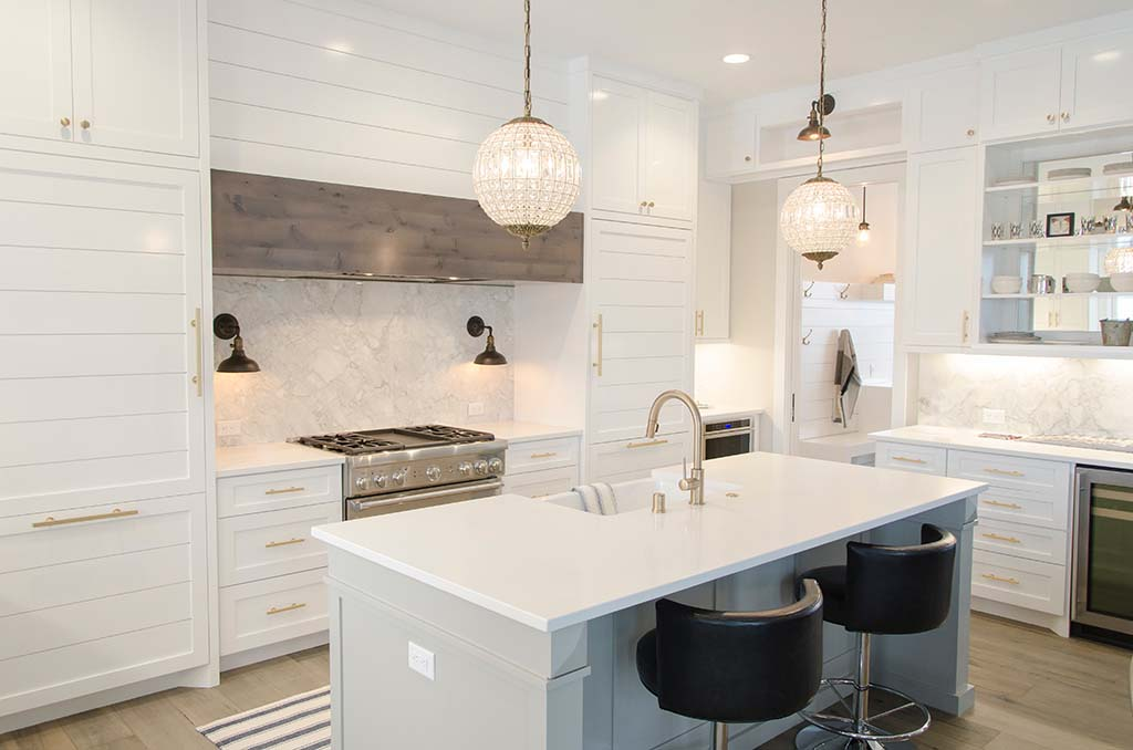 A stylish white kitchen with a large white island and chandelier pendant lights over it.