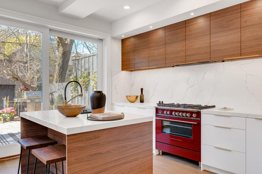 A contemporary kitchen with an island, lots of wooden detail and a deep red stove.