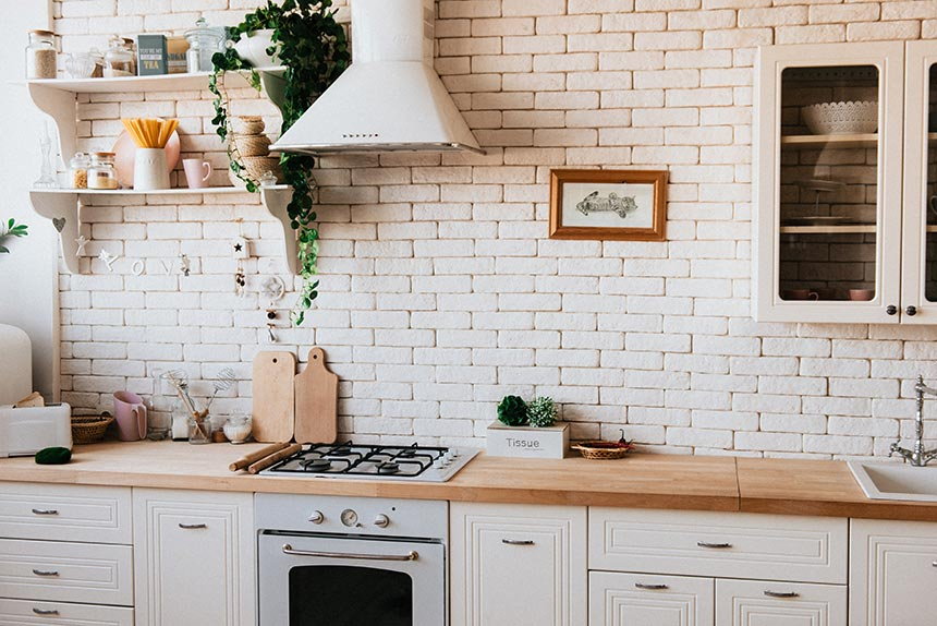 A farmhouse style kitchen with a wooden countertop and off white brick wall accent as a backsplash.