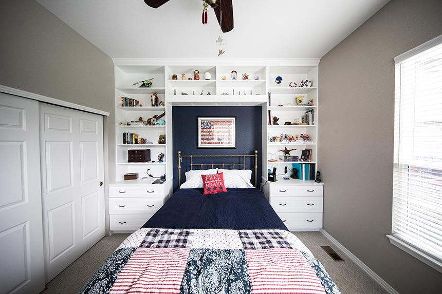 A stylish boy's bedroom with a built bookcase around the bed.