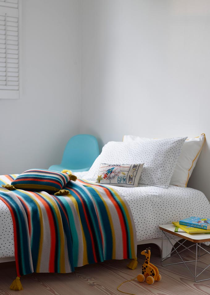 A nicely made kids bed with a striped colorful throw on it. Image by Christy.