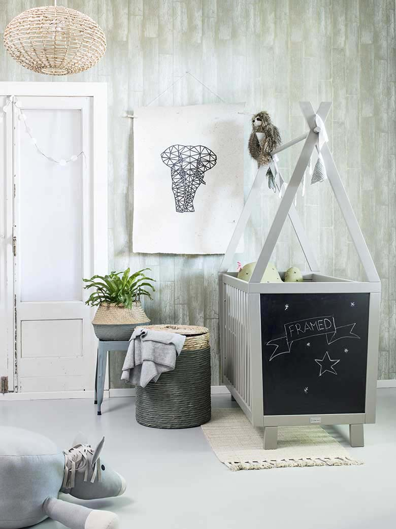 What a beautiful nursery with a soft sage green wall color, white furniture and a blackboard on the bottom end of the cot bed! Image by Cuckooland.