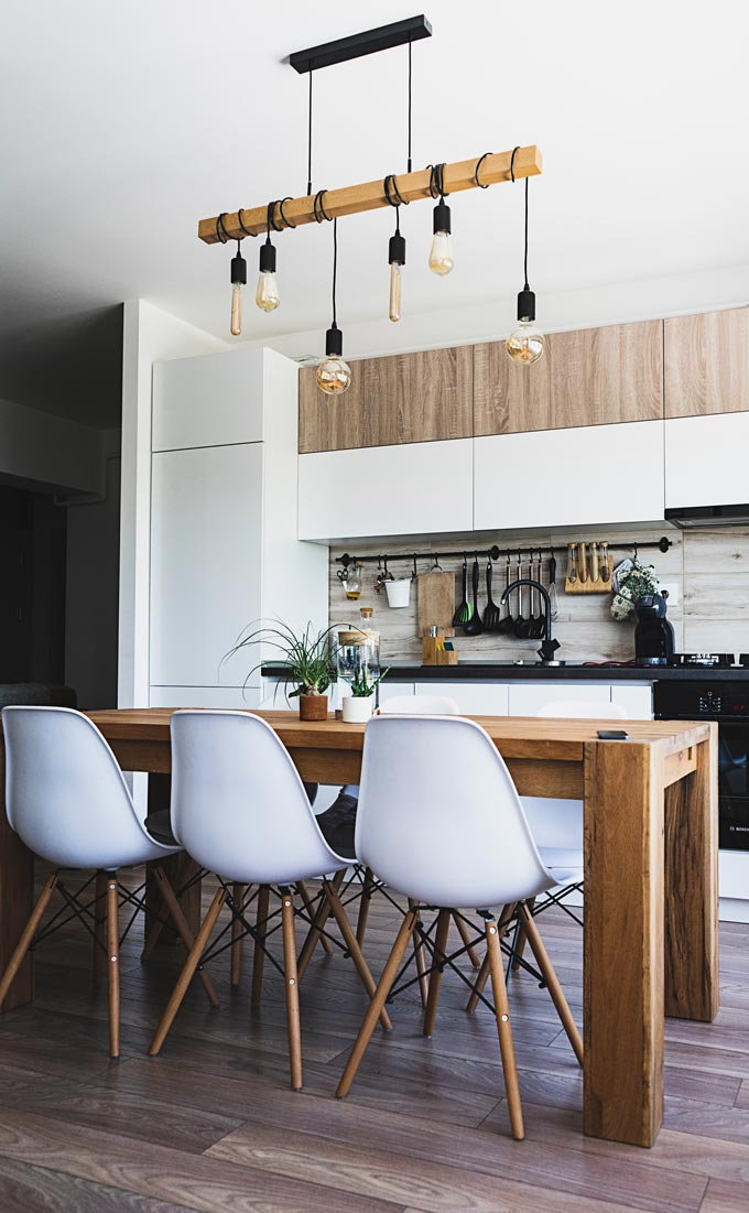 A contemporary kitchen with white cabinetry and a large wooden dining table in the foreground.