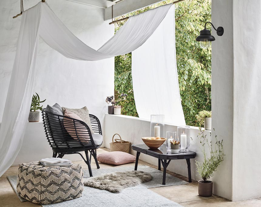 What a dreamy outdoor setup with a black rattan chair, a chevron pattern pouf, and an airy canopy. Image via John Lewis.