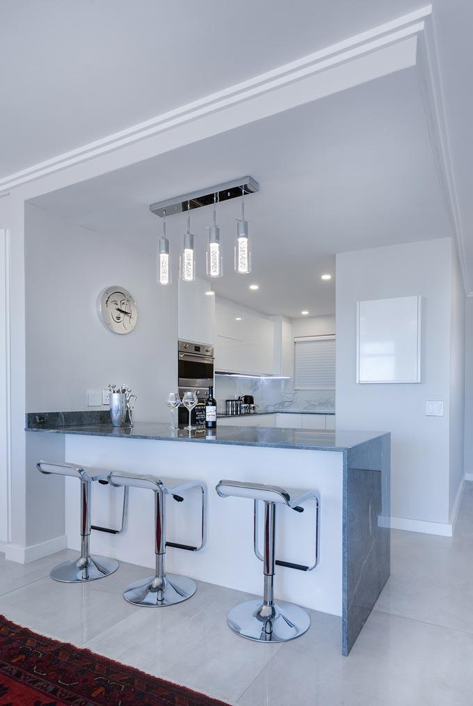 A modern minimalist kitchen with a bar bridge made of a grey marble.