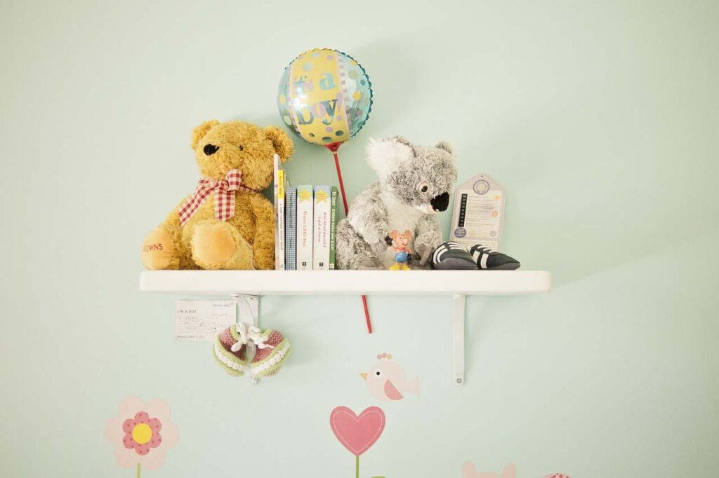 A white shelf against a light green wall with decor for babies (little books and cuddle toys) as part of a nursery