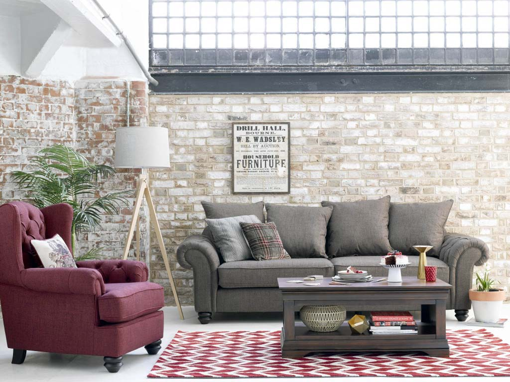 An interior with a gray sofa, a red wine armchair, a floor lamp in between, an area rug with a red wine chevron pattern and a brick accent wall