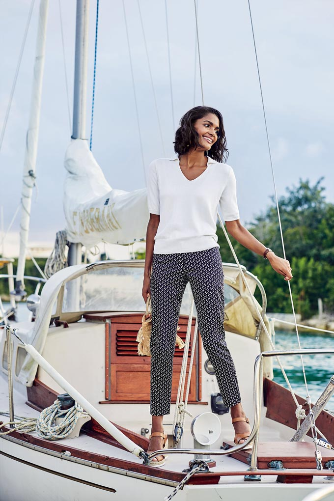 A stylish woman wearing a chevron pattern pair of pants and a white tee while on a docked sailboat. Image via Pure Collection.
