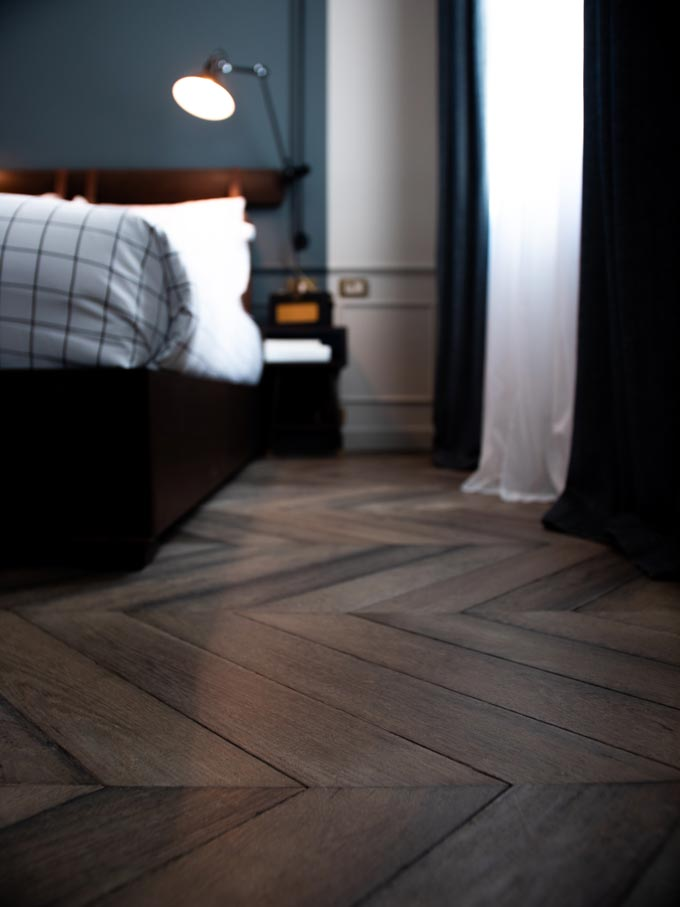 A bedroom with a blue accent wall in the background and dark chevron pattern hardwood flooring.
