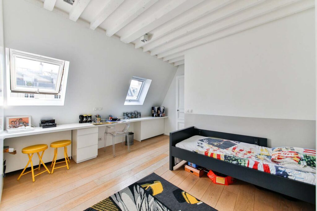 A boy's room with a dark bed, white desk space, hardwood floor, white exposed beams on ceiling and a colorful rug on the floor
